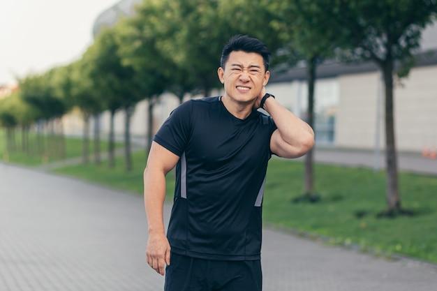 남자 아시아 운동선수, 일하기 전에 배낭을 메고 공원에서 뛰고, 경기장 근처 공원에서 뛰는 것은 통증에 지친 심한 목 통증을 가지고 있습니다