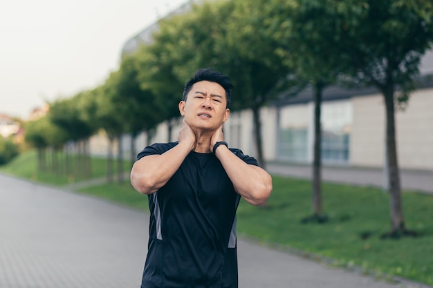 Male asian athlete, running in the park in a backpack before work, running in the park near the stadium has severe neck pain tired of pain