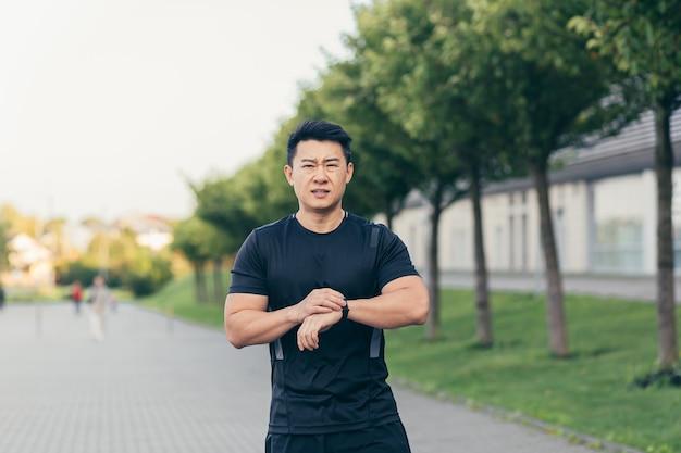 Азиатский спортсмен, усталый после утренней пробежки, бежит в парке возле стадиона