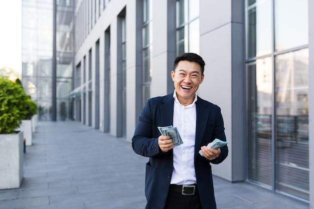 男性のアジア人ビジネスマンはお金を与えるカメラを見てたくさんの現金を持って喜ぶ