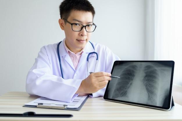 オフィスの病院で働く男性のアジア医師。デジタルタブレットを使用してx線について議論します。
