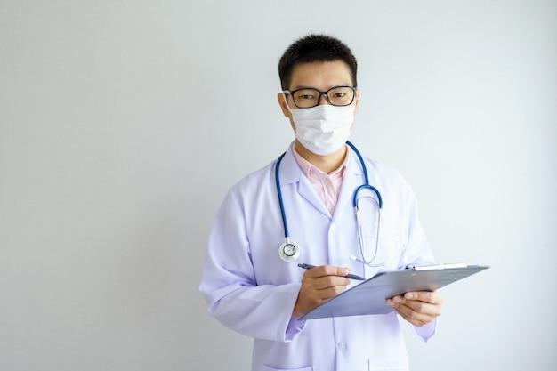 フェイスマスクを身に着けているオフィスの病院で働いている男性のアジアの医者はcovid 19ウイルスを保護します。