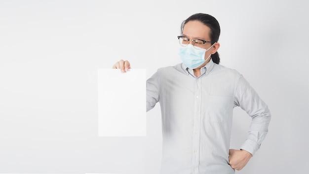 男性のアジア人の手は、a4白紙を保持し、白い背景でフェイスマスクとストリップシャツを着ています。