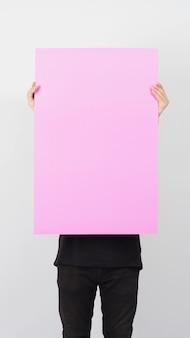 Мужская азиатская рука держит чистый лист розовой бумаги на белом фоне.