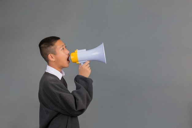 A male asian student wearing a black sweater using a megaphone and standing on a gray .