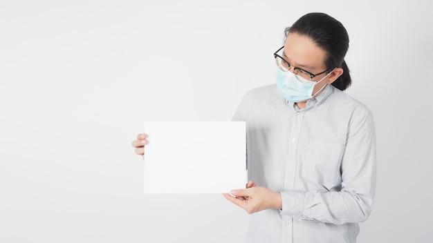 男性のアジア人はフェイスマスクとストリップシャツを着用し、手は白い背景にa4紙を保持しています。