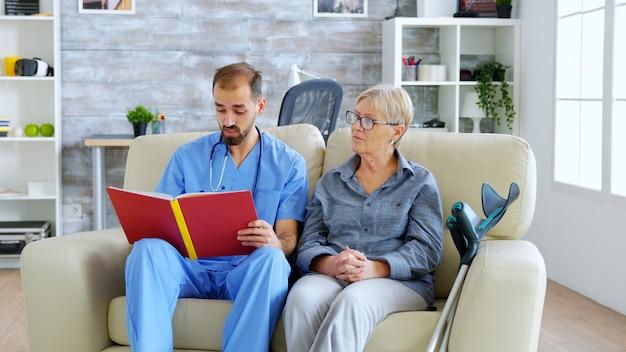 은퇴한 노인 연금 수급자에게 책을 읽는 요양원의 남성 조수. 간병인 및 사회 복지사