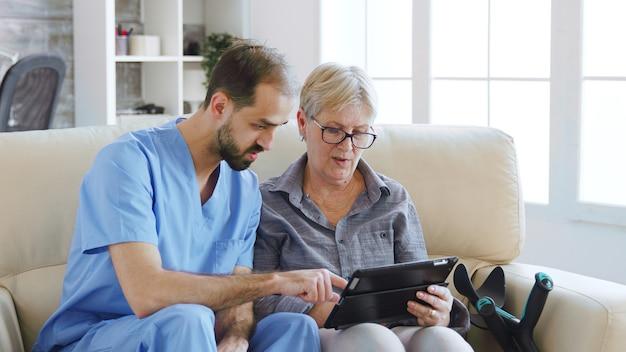 은퇴한 노인 노인에게 치료를 위해 요양원에서 태블릿 컴퓨터를 사용하는 방법을 가르치는 남성 조수