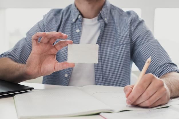 Мужчина в офисе держит визитку