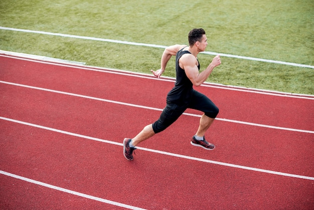 Male athlete arrives at finish line on racetrack during training session