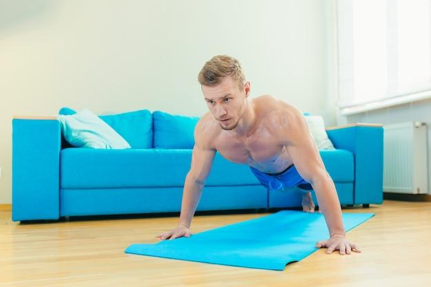 Спортсмен-мужчина дома занимается фитнесом в гостиной