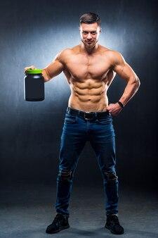 Бодибилдер-мужчина держит банку спортивного питания