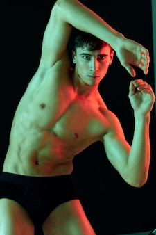 Male athlete on a dark background posing and showing muscles on the abdomen