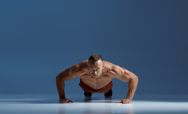 Male athlete doing abs exercise, workout in studio
