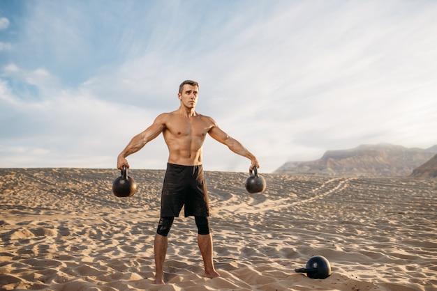 Спортсмен-мужчина делает упражнения с двумя гирями в пустыне в солнечный день. сильная мотивация в спорте, силовые тренировки на свежем воздухе