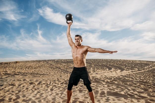 Спортсмен-мужчина делает упражнения с весами в пустыне в солнечный день. сильная мотивация в спорте, силовые тренировки на свежем воздухе