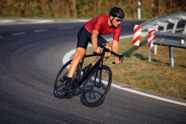 아스팔트 도로를 타기 위해 검은 자전거를 사용하는 스포츠 의류, 미러 안경 및 보호 헬멧을 입은 남성 운동 선수