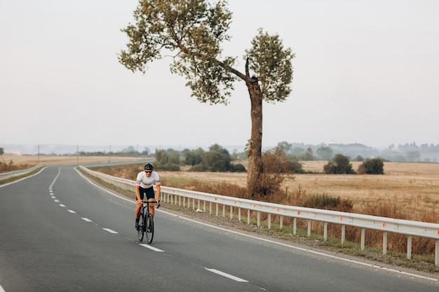 アスファルト道路でのスポーツ活動のために黒い自転車を使用してスポーツウェアを着た男性アスリート
