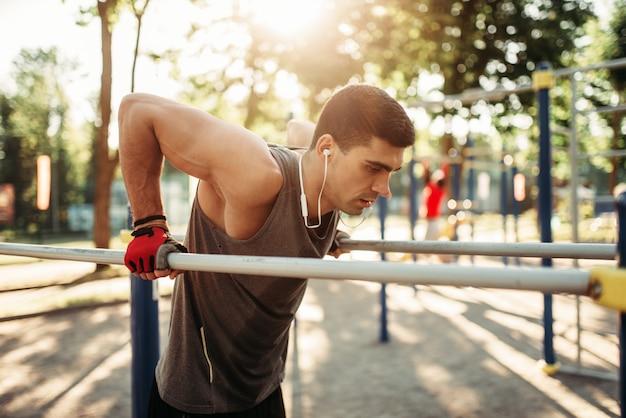 Спортсмен мужского пола упражнения на брусьях открытый