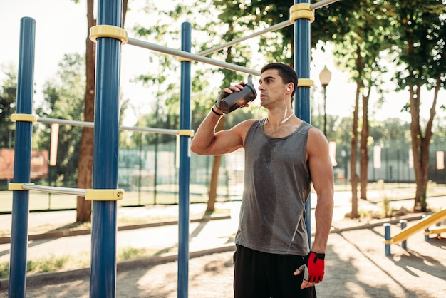 Male athlete in headphones drinks water after outdoor fitness training. strong sportsman on sport workout in summer park