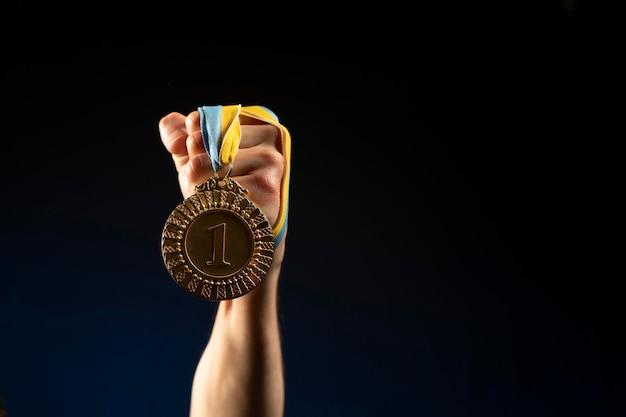 Спортсмен-мужчина держит медаль