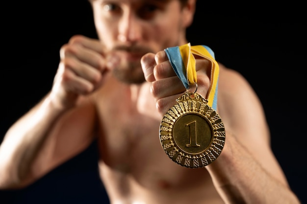 Спортсмен-мужчина держит медаль олимпийских игр