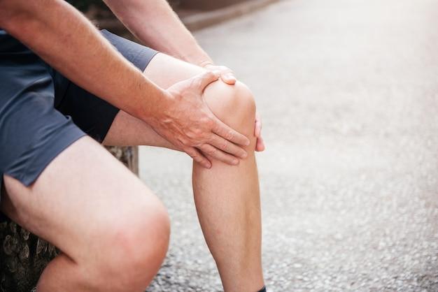 膝を抱えて捻挫膝の怪我をしている男性アスリート