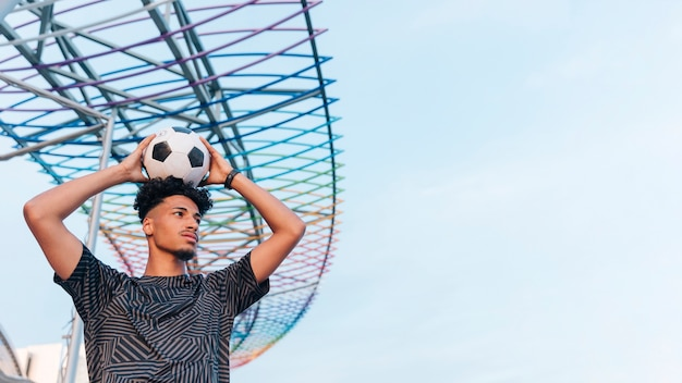 Male athlete holding soccer ball above head against blue sky