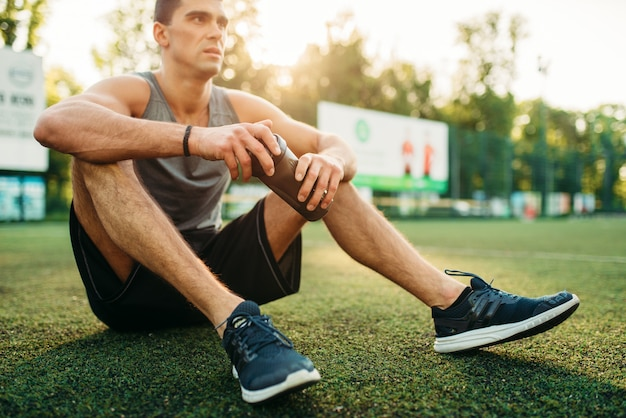 Male athlete holds bottle of water, relax after outdoor fitness workout. strong sportsman sitting on a grass in park