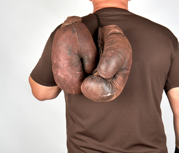 Male athlete holds a pair of very old vintage boxing gloves