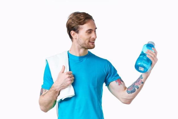 병에 음료와 그의 어깨에 수건으로 파란색 티셔츠에 남자 선수. 고품질 사진