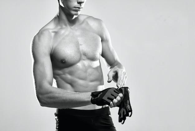 스포츠 장갑을 낀 남자 운동 선수는 언론 운동 피트니스를 펌핑했습니다.