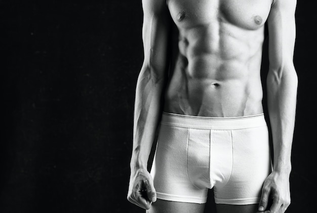 白いショートパンツの男性アスリートは、暗い背景を膨らませたボディービルダー