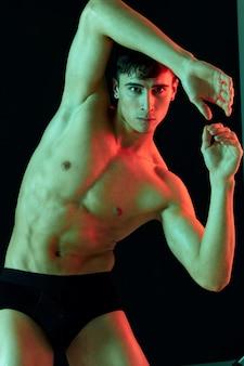 暗い背景に男性の運動選手がポーズをとり、腹部の筋肉を見せる