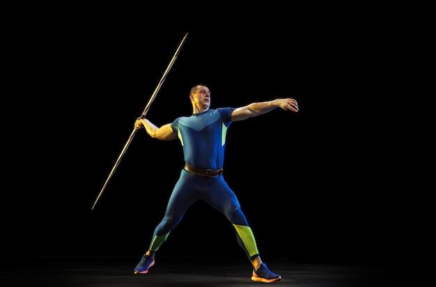 暗闇の中でやり投げを練習している男性アスリート
