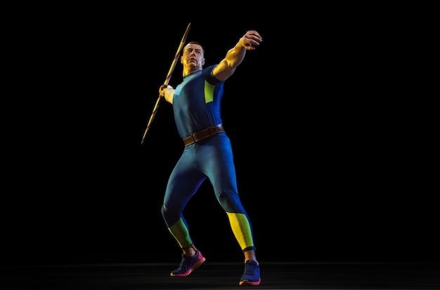 ネオンの光の中で黒いスタジオで孤立したやり投げで練習している男性アスリート
