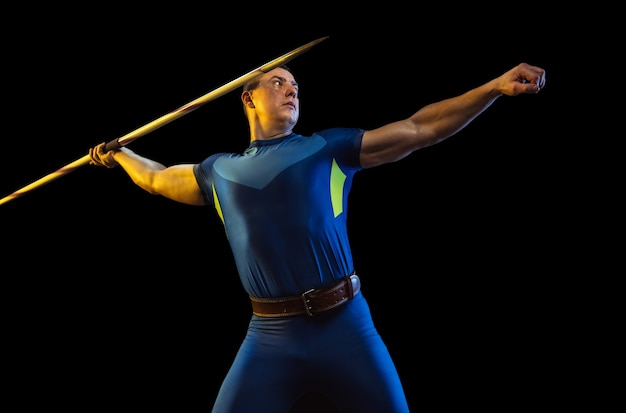 네온 불빛에 검은 스튜디오에 고립 된 창 던지기 연습 남자 선수