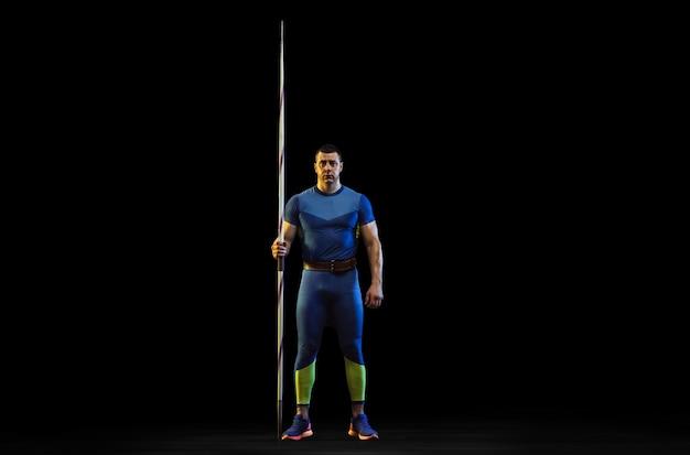 ネオンの光の中で黒い背景にやり投げを練習している男性アスリート。自信を持ってポーズをとるプロスポーツマン。健康的なライフスタイル、動き、活動、競争の概念。コピースペース。