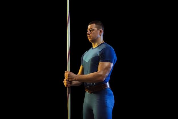ネオンの光の中で黒にやり投げを練習している男性アスリート。