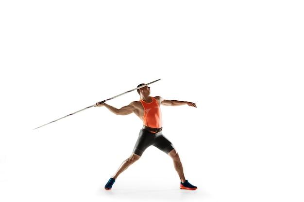白いスタジオでやり投げの練習をしている男性アスリート。