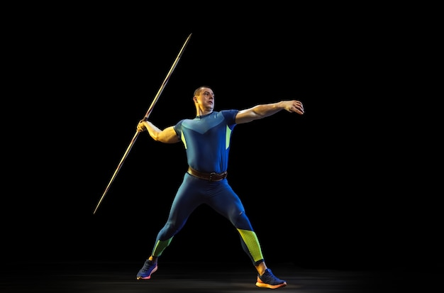 Male athlete practicing in throwing javelin in the dark