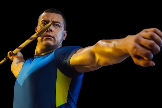 Male athlete practicing in throwing javelin in the dark