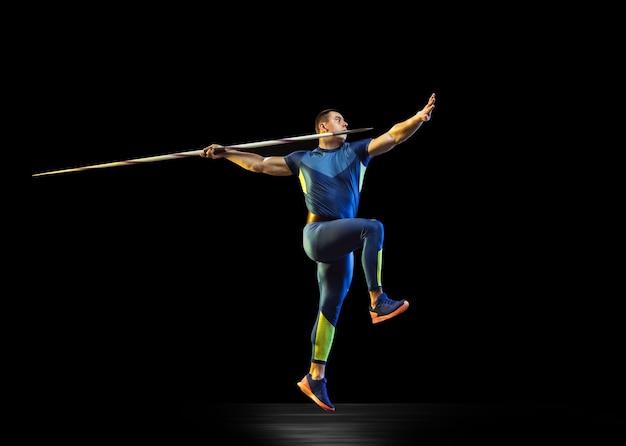 Atleta maschio che pratica nel lancio del giavellotto nel buio