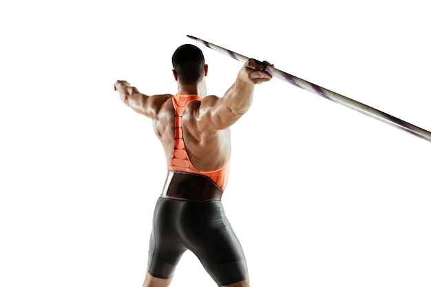 Male athlete practicing in throwing javelin on white studio.