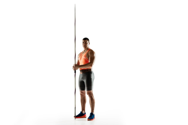 Male athlete practicing in throwing javelin on white.