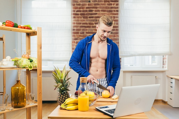 Спортсмен-мужчина готовит салат и свежий фруктовый сок дома на кухне