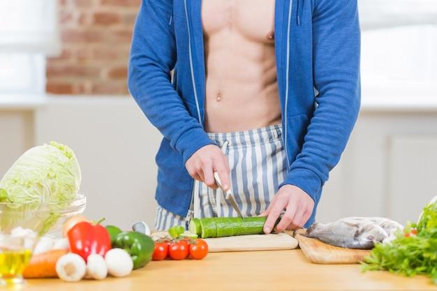 부엌에서 집에서 건강 식품을 준비하는 남자 선수