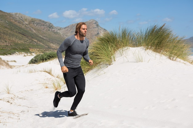 Male athlete running at beach by mountain