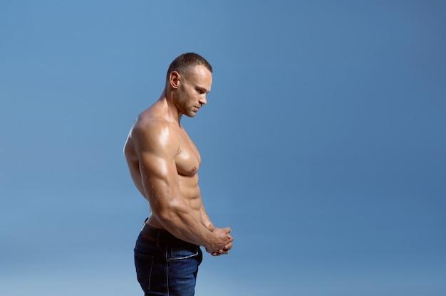 Спортсмен-мужчина показывает свои бицепсы в студии, вид сбоку