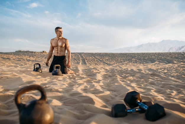 Male athlete sitting on sand after workout in desert at sunny day. strong motivation in sport, strength outdoor training